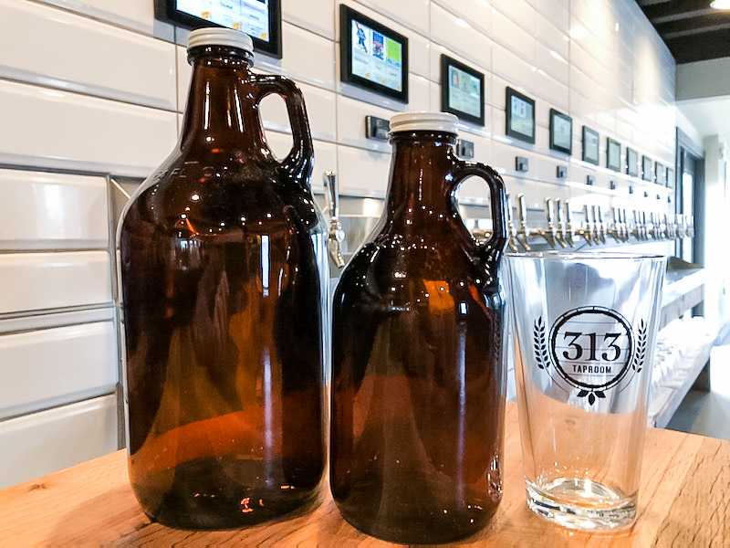 Growlers and a pint glass from 313 Taproom