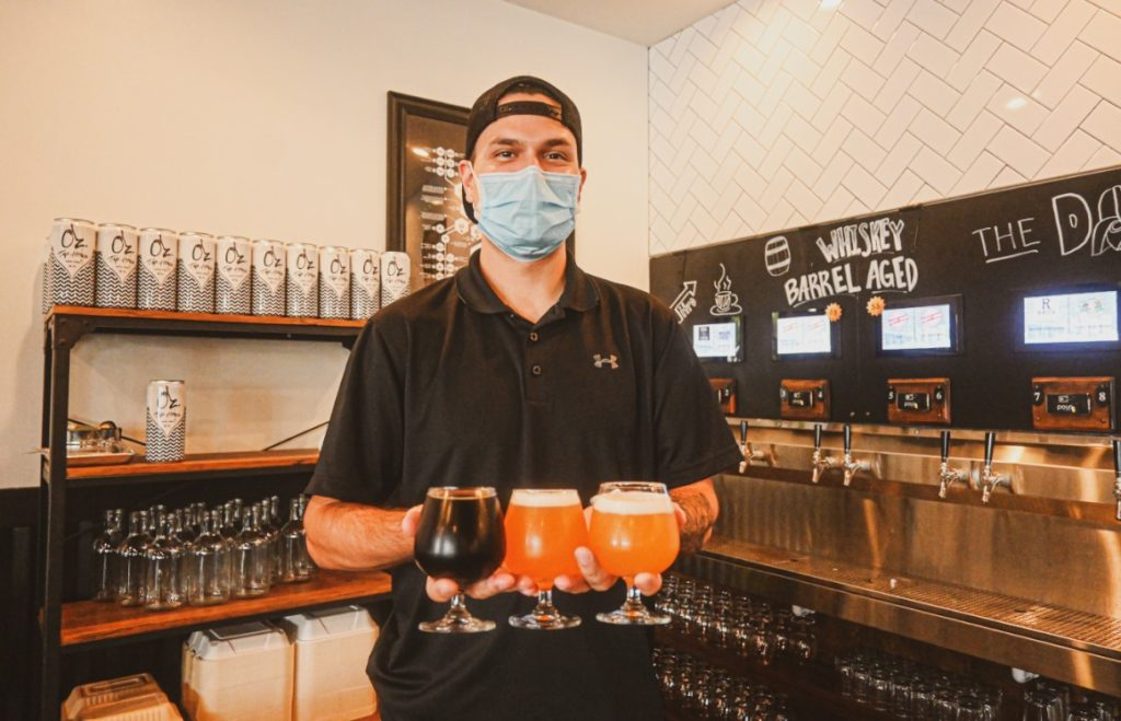 Staff member in mask at Oz. Tap House