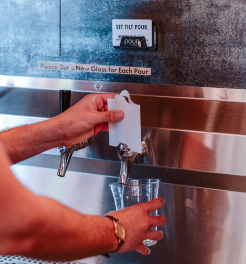 Pouring from PourMyBeer self-serve beverage wall with Tapkin